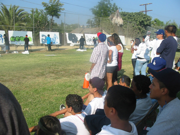 Students gather at Franklin High School football field to watch participants produce art for the Aerosol Art competition.