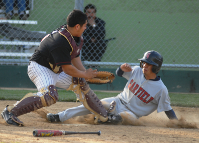 Garfield High's Oscar Preciado slides home safely before Roosevelt catcher Luis Ceja can apply the tag in last week's Eastern League game. Garfield won, 9-2. (EGP photo by Mario Villegas)