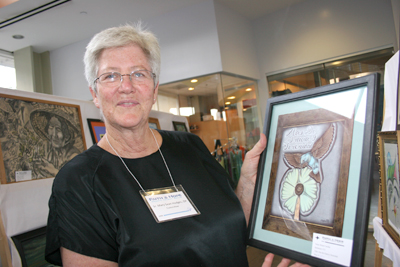 """Sister Mary Sean Hodges holds up """"Alas de Gracia y Serenidad"""" by Rafael Casillas, as an example of a color illustration created by a prisoner without access to conventional paint or colored pencils colors. (EGP Photo by Gloria Angelina Castillo)"""