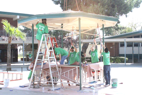 Volunteers on Oct. 12 paint a Schurr High School kiosk used to sell tickets for campus events. (Courtesy of MUSD)