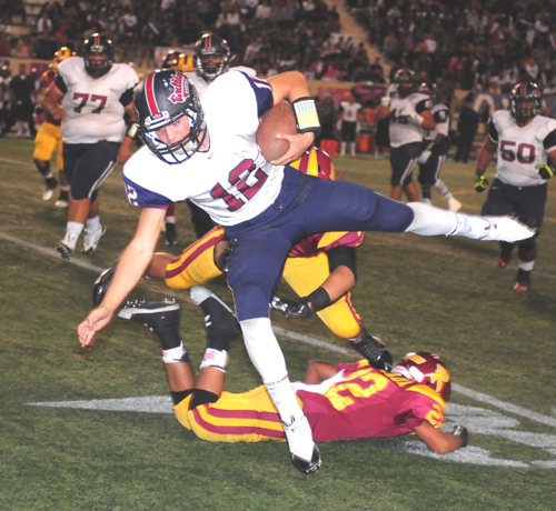 Garfield High School quarterback Ausencio Navarro leaps for a gain in last Friday's 79th East Los Angeles Classic. Garfield defeated Roosevelt, 22-6. (EGP photo by Mario Villegas)