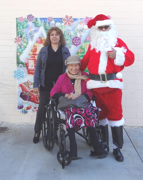 HSA client Lucille Lefto , middle, poses with Santa. (Elizabeth Ruiz for HSA)
