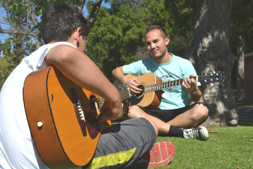 Recreation staffer Steven Cole plays the guitar with a client.  (Courtesy of Hillsides)