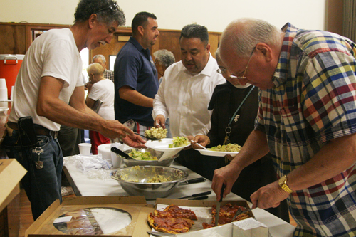 "Monsignor John Moretta, right, and Boyle Heights resident Miguel Alfaro, left, serve food at Resurrection Church, during a 'celebratory"" gathering Monday.   (EGP photo by Nancy Martinez)"
