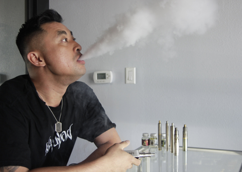 Vape Unit owner Andy Han uses his electronic-cigarette at his Monterey Park shop Tuesday. (EGP photo by Nancy Martinez)