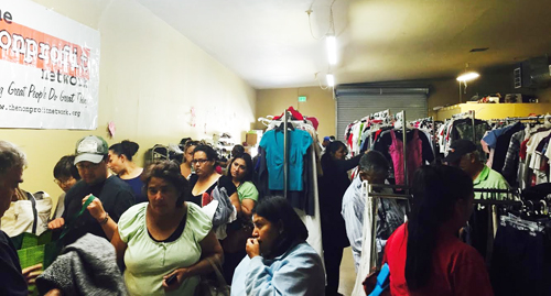 People pick out five free articles of clothing at a weekly clothes distribution by Plaza Community Services in East Los Angeles last week. The non profit will recieve a grant  by the Vernon CommUNITY Fund to help continue the service. (Photo courtesy of Plaza Community Services )