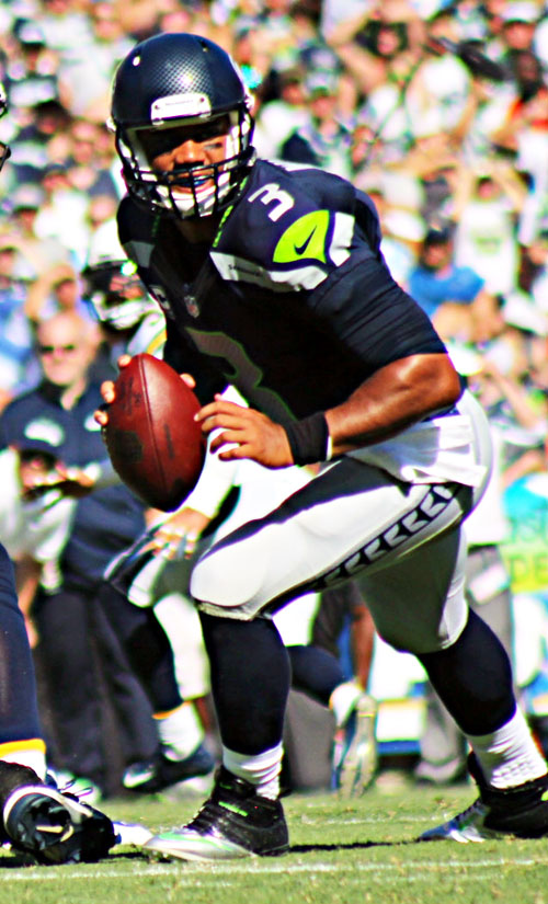 Seattle QB Russell Wilson (pictured) passed for 3,475 yards and 20 touchdowns with 7 interceptions, and rushed for 847 yards and 6 touchdowns during the 2014 regular season.  (Photo by Fred Zermeno)