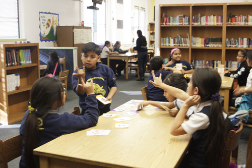 "Brian Tzep, 9, practices signing ""I love you"" with fellow Woodcraft Ranger Ashey Castillo, 8, Monday during after-school American Sign Language class. (EGP photo by Nancy Martinez)"