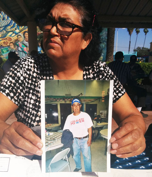 Maria Leandra Reyes holds an old photo of her long time friend Jesus Valderrama, who was fatally hit by a car at Ruben Salazar Park Mar. 10. (EGP photo by Jacqueline Garcia)