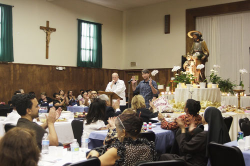 Assistant U.S. Attorney Joseph Johns, center, is applauded by Eastside residents during a special dinner at Ressurection Church Sunday night.  (EGP photo by Nancy Martinez)
