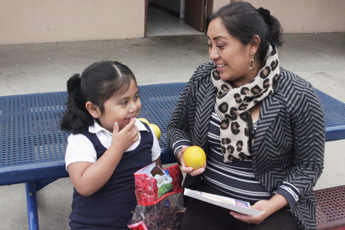 Areli Lopez talks to her 5-year old daughter about eating fruits and vegetables.  (EGP photo by Nancy Martinez)