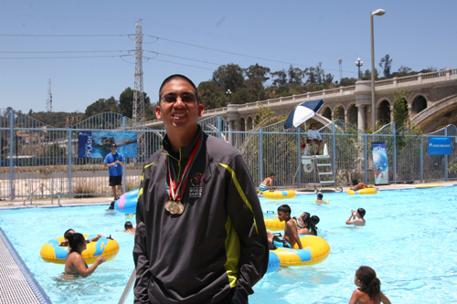 Joshua Fontelera, 23, proudly wears medals he has won in past competitions during Operation Splash kick-off event Monday. (EGP Photo by Jacqueline Garcia)