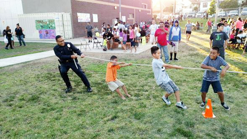 LAPD officers play a game of tug-of-war with children during the Summer Night Lights program in Highland Park. (Courtesy of Highland Park Neighborhood Council)