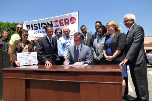 Los Angeles Mayor Eric Garcetti, center, signs an executive directive at a desk in the middle of a Boyle Heights street Monday. (Office of Los Angeles Mayor Eric Garcetti)