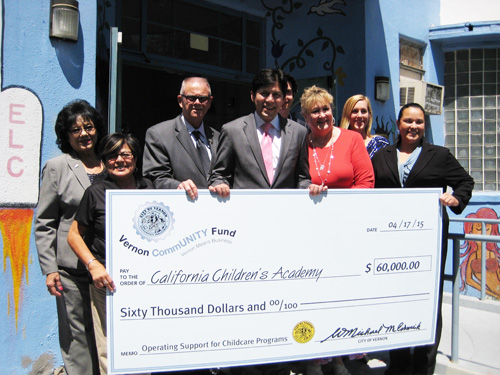Senator Kevin de Leon, pictured center, joins Vernon Mayor W. Michael McCormick, third left, and Councilwoman Luz Martinez, second left, at a check presentation at the California Children's Academy earlier this year. (City of Vernon)