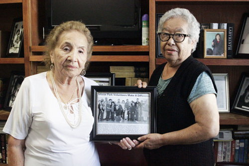 Martha Fuentes, left, and Angelica Rodriguez, right, hold a framed newspaper clipping where Salazar Park seniors were recognized. (EGP photo by Nancy Martinez)