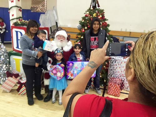 After receiving their toys, Arlene Hernandez (right) takes a photo of her children with Santa Claus. (Office of Assemblyman Jimmy Gomez)
