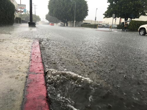 Heavy rain flooded streets in Lincoln Heights Tuesday, causing some traffic incidents. (Photo by Nancy Martinez)