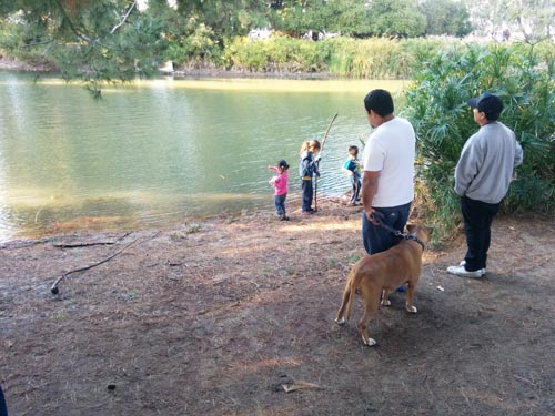 Reyes Rosales watches his children as they play along the lakeside, which has lost a significant amount of water. (EGP photo by Jacqueline Garcia)