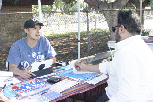 Volunteers register voters Wednesday at Lincoln Heights Farmers Market. (EGP photo by Jacqueline Garcia)
