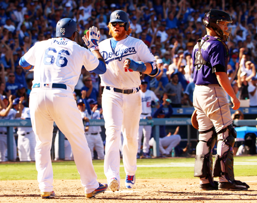 Yasiel Puig greets Justin Turner at home plate in the seventh inning with a high five to keep the game alive. (Photo by Fred Zermeno)