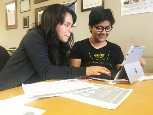 Andrea Luna, left, and Suzette Aguirre, right, compile their findings on the impacts of lead contaminated soil, which will be presented Friday. (EGP photo by Nancy Martinez)