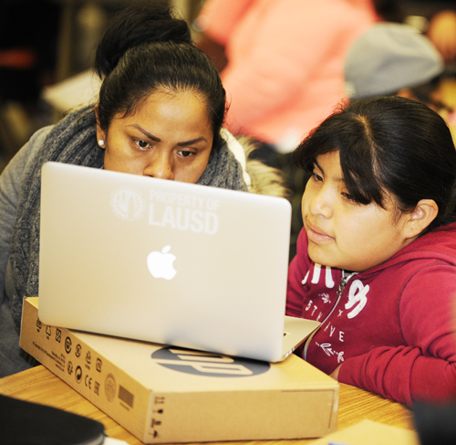 Aurea Gonzalez, left, and her daughter Stevenson Middle School student Karen Jaimez are fully engaged as they learn about the resources their new device has to offer them.