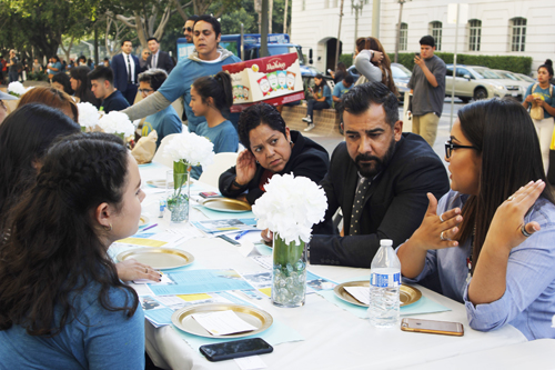 Jackie Vargas, right, discusses the importance of involving youth in the city;s budget process with representatives from the mayor's office Tuesday at a table set up outside L.A. City Hall. (EGP photo by Nancy Martinez)