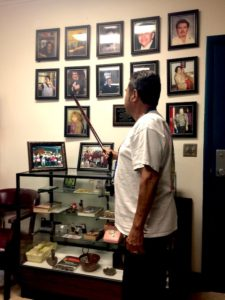 Salazar Park volunteer Ray Guerrero uses his cane as a pointer, as one by one Angeles Support Group members names the volunteers whose photos have made it on to the memorial wall. (EGP photo by Gloria Alvarez-August 1, 2017)