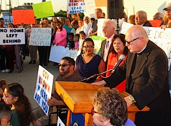 At a press conference in Commerce Monday, Monsignor John Moretta (center), joined by hundreds of community activists and elected officials demanded the Dept. of Toxic Substances Control include parkways and home interiors in its Exide clean up plan. contamination zone. (EGP photo by Fred Zermeno)