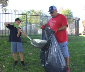 Adrian Vega, 6, participates in Saturday's cleanup of Montebello City Park. Vega was assisted by Ricardo Ramirez, who enjoys teaching scout members about giving back to the community of Montebello. ((EGP photo by Carlos Alvarez)