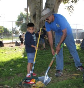 St. Benedict Church Cub Scout Pack 0476 Master Jose Soto teaches eight-year-old Aden Munoz how to properly rake and pickup leaves during Beautification Day at Montebello City Park. Soto said that this is a way to teach kids to respect and give back to their community. (EGP Photo by Carlos Alvarez)